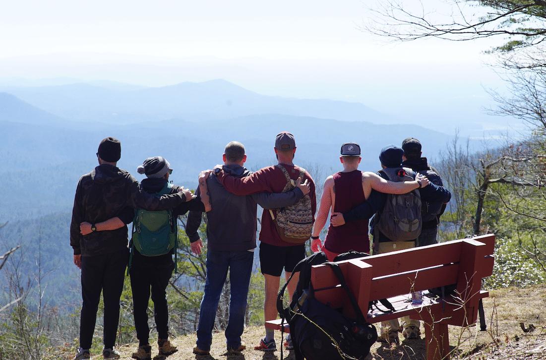 men hugging on a mountain